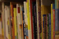 Children's books on a shelf, via phys.org